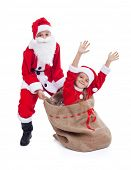 Christmas surprise- kids dressed as santas having fun with large bag, isolated