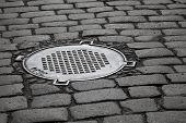 Old Sewer Manhole On Dark Cobblestone Pavement