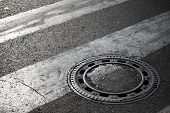 image of pedestrian crossing  - Sewer manhole cover on dark asphalt road with pedestrian crossing marking - JPG