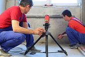 Two workers makes measurements with laser level tool in a niche for radiators in apartment with a ro