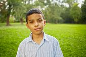 Closeup portrait of mulatto boy in light-blue striped shirt