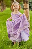 Little girl in beautiful violet gown and crown on head stands  on grassy lawn in park, lifting up sl