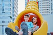 Boy and his younger sister sit at bottom of slide on children playground in house yard