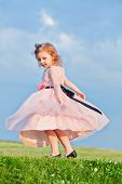 Little girl dressed in light-rose gown turns on grassy meadow and hem of her dress flutters