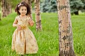 Little mulatto girl with ring on finger in beige party frock stands between trees in park