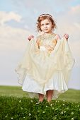 Little girl in beautiful beige gown and crown on head stands  on grassy meadow, lifting up slightly hem of external skirt
