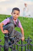 Little boy dressed in suit with vest sits on black wrought-iron fence, figure of little girl behind him not in focus