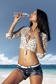 beautiful girl drinks water from bottle, thirst in hot day