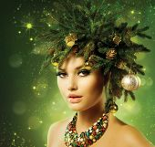 Christmas Woman. Beautiful New Year and Christmas Tree Holiday Hairstyle and Make up. Beauty Fashion Model Girl Portrait