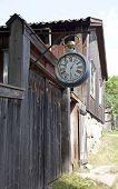 Wooden clock hangs above a street.