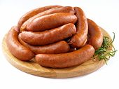 stock photo of grease  - Many fresh sausages on round cutting board - JPG