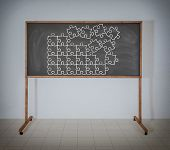 stock photo of brain teaser  - Puzzle on a black school blackboard  in room - JPG