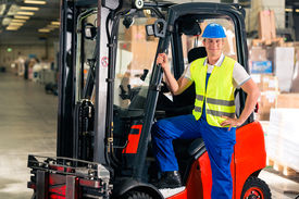 pic of forklift  - forklift driver in protective vest and forklift standing at warehouse of freight forwarding company - JPG
