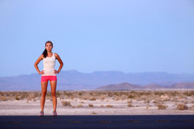 image of late 20s  - Athlete runner woman resting on road after running on highway in the USA - JPG