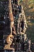Ancient stone faces of Bayon temple, Angkor, Cambodia on sunset