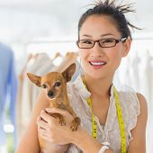 Portrait of a beautiful female fashion designer with chihuahua in the store