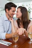Loving happy young woman showing engagement ring besides man at home
