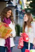 stock photo of african american hair styles  - Two attractive young happy women walking in an urban city environment and carrying Christmas gifts - JPG