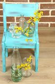 Beautiful Forsythia blossom in transparent jars on brick wall background