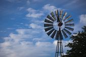 stock photo of wispy  - Majestic Windmill Against a Deep Blue Sky and Wispy Clouds With Room For Text - JPG