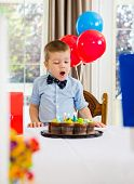 Birthday boy with mouth open looking at cake
