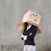 Businesswoman in suit wearing carton box on head