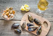 Mussels With A Glass Of White Wine On The Wooden Table