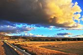 The enormous storm cloud and a flat plain covered in orange sunset.  In the steppe runs a gravel roa