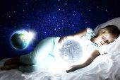 Girl lying in bed with moon in hands. Elements of this image are furnished by NASA