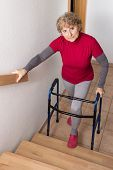 picture of stairway  - Retiree standing with walker in front of a stairway - JPG