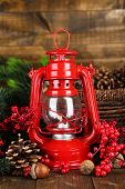 image of kerosene lamp  - Red kerosene lamp on wooden table on wooden background - JPG