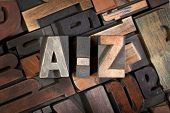 a-z written with vintage letterpress printing blocks on random letters background