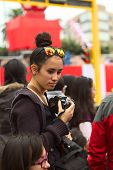 Young Woman with Camera at Wong Parade in Lima, Peru