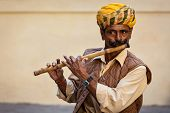 JODHPUR, INDIA - NOVEMBER 26, 2012: Indian man plays wooden flute in Mehrangarh fort, Rajashtan, Ind