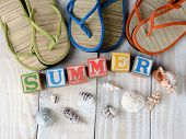 Childrens blocks spelling out Summer on rustic wooden boards The word is surrounded by sea shells, a