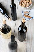 Wine still life shot from a high angle. Five bottles of wine with a cork screw napkin and bowl of co