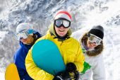 stock photo of young men  - Portrait of three happy young men with snowboards in googles - JPG