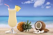 stock photo of pina-colada  - Pina Colada cocktail with fruits on the beach while on vacation - JPG