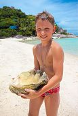 Big Seashell Held By A Young Boy On The Beach