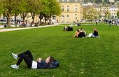 STUTTGART, GERMANY - APRIL 01, 2014: Young people rest on the grass in a Park near the Central square of Stuttgart (Schlossplatz)