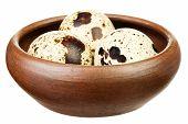 Three quail eggs on a brown plate