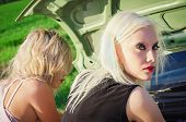 Two Blonde Girls Stand By The Broken Car