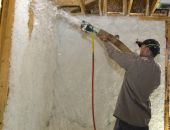 stock photo of insulator  - Worker blowing insulation into the wall of a newly framed house