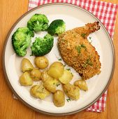 Chicken Kiev served with broccoli and new potatoes.