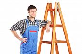 Male worker in jumpsuit standing next to a ladder isolated on white background