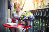 Attractive young girl reading book while drinking coffee at sunny day sitting on the balcony