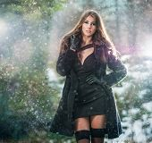 Portrait of young beautiful woman outdoor in winter scenery. Sensual brunette with long legs