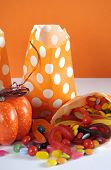Row Of Happy Halloween Orange Polka Dot Trick Or Treat Paper Bags With Multi-color Candy Against And