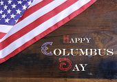 picture of wood  - Happy Columbus Day greeting message text on dark rustic recycled wood background with USA stars and stripes flag - JPG