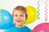 Little boy with festive balloons and streamer